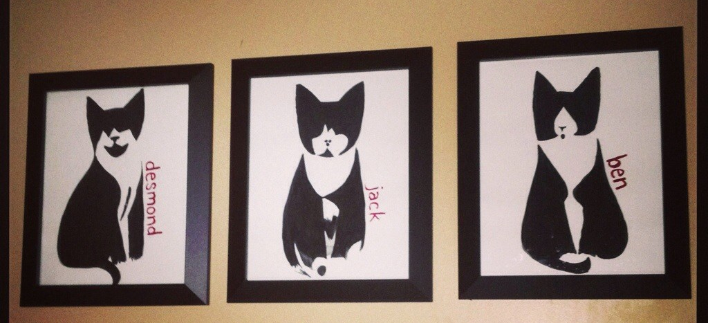 Three paintings of tuxedo cats