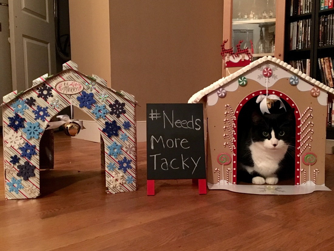 Tuxedo cat sits inside fully decorated cat house
