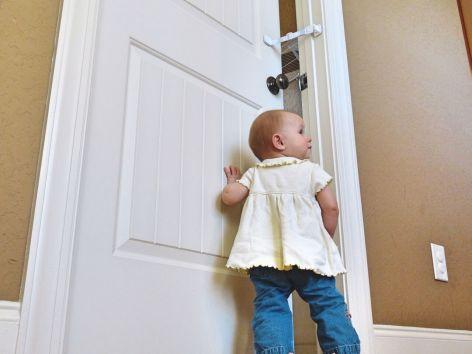 Photo of baby unable to open door with Door Buddy in use